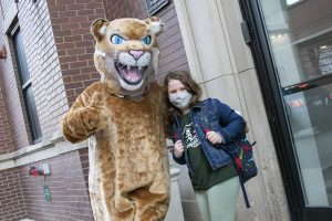 student with mascot outside school