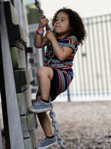 student climbing on outdoor playground equipment
