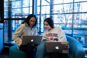 2 students look at their Mac laptops